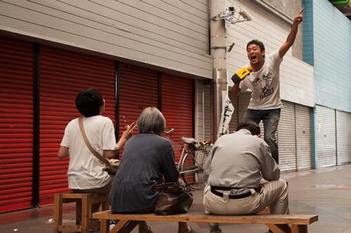 春雄、シャッター商店街の真ん中で老人相手にマメカラでライブ