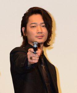 拳銃を構えてポーズをとる綾野剛、映画『日本で一番悪い奴ら』初日舞台あいさつにて