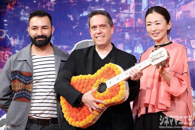 マリーゴールドの花をあしらったアコースティックギターを手に、左からエイドリアン・モリーナ共同監督、リー・アンクリッチ監督、松雪泰子
